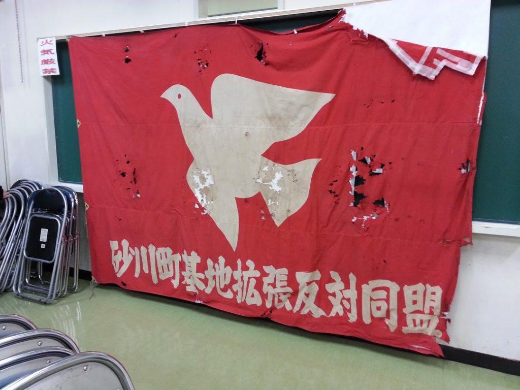 会場後ろに、当時を伝える風雪に耐えた「反対同盟」の旗が飾られていた