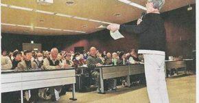 俳句が掲載された会報を手に語るさいたま市の女性(信濃毎日新聞)